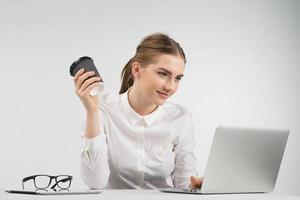 Smiling business woman sitting and working behind a laptop holding cup of coffee and looking at the screen photo