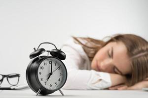Closeup alarm clock in focus against blurring background with  girl puts her head on the table photo