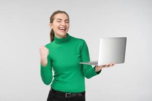 Happy girl looking at laptop with laughing surprised expression . Holds device and fist up. - Concept image photo