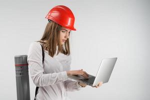 Mujer arquitecta se encuentra con un tubo detrás de su espalda sosteniendo la computadora portátil y mirando a la pantalla foto