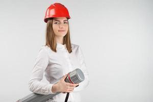 Mujer sonriente se encuentra en casco naranja sostiene el tubo de cerca foto
