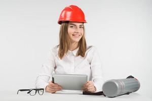 Mujer feliz arquitecto en casco naranja sostiene el ipad y se sienta junto al tubo, gafas foto