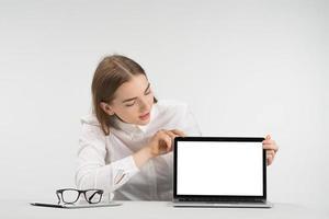 mujer bonita se sienta a la mesa y mira la pantalla. concepto de maqueta foto