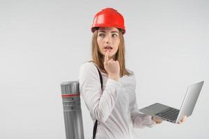 Mujer arquitecta se encuentra con un tubo detrás de su espalda sosteniendo una computadora portátil y mirando hacia otro lado perdido en sus pensamientos foto