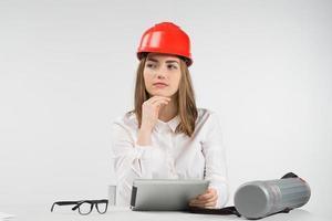 Mujer especulación se sienta a la mesa en casco naranja sostiene ipad foto