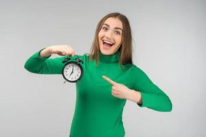 Laughing happy woman wearing casual clothes standing and holding alarm clock. Pointing to the clock photo