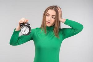 Young woman wearing casual clothes standing isolated over  background holding alarm clock - Image photo