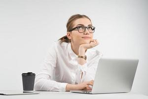Smiling business woman sitting behind a laptop with a cup of coffee and ipad on the table and looking up dreamy photo