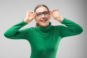 Smiling girl in glasses posing in studio  and looks sideaway happily. - Image photo