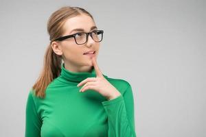 joven con gafas de pie es pensativa en el estudio y mirando hacia arriba. - imagen foto