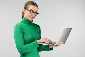 Woman  in half-turn works on a laptop while standing. Looking  at the camera photo