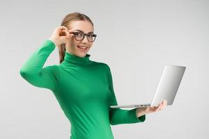 Cheerful woman in glasses works on a laptop holding it in her hands  while standing against on the white background. Looks at the camera photo