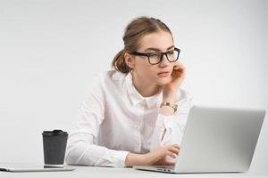 Smart business woman sitting  and carefully working behind a laptop with a cup of coffee and ipad on the table photo