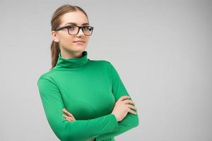 Serious  young woman  in glasses and in casual clothes posing in the studio with crossing hands. Horizontal image photo