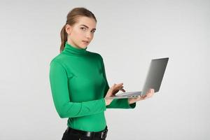 Woman in half-turn works on a laptop holding it in her hands  while standing against on the white background. Looks at the camera photo