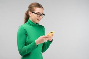 Pretty woman in the glasses holds  her iphone  and  reads a message photo