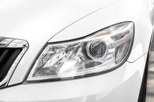 Modern and elegant white car - Closeup of car headlight photo