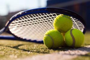 Imagen macro de tres pelotas de tenis y raquetas en cancha dura bajo la luz del sol foto