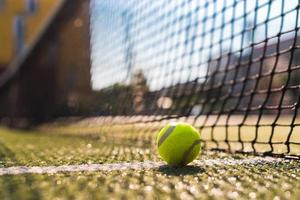 Closeup pelota de tenis acostado sobre la línea blanca en la cancha dura junto a la red foto