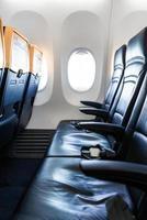 interior del avión - cabina con silla de cuero moderna para el pasajero del avión. asientos de aviones y ventana. - imagen vertical foto