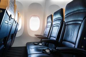 interior del avión - cabina con silla de cuero moderna para el pasajero del avión. asientos de aviones y ventana. - imagen horizontal foto