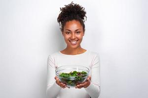 Closeup portrait of woman standing with bowl of salad over wite background photo