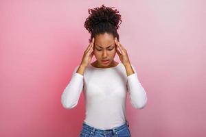 Studio portrait mulatto touching pressed herself head with her hands.Concept headache photo