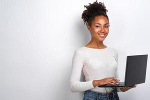 Portrait of happy young woman holding laptop computer over white background photo