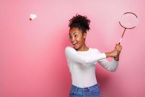 Chica guapa jugando al bádminton en el estudio con emoción de felicidad foto