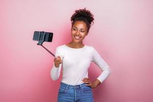 Young girl holding mobile phone takes a picture selfie - Image photo