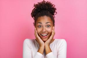 Closeup retrato de una niña bonita sobre fondo de color rosa con asombrada emoción en la cara - imagen foto