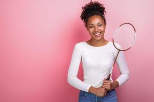 Sporty girl standing with badminton racket in the studio looking at the camera photo