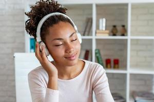 Portrait of a delightful girl with closed eyes in earphones listening to music - Image photo