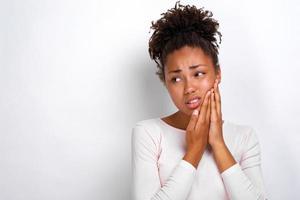 Retrato de estudio de mujer enferma se toca la mejilla y parece infeliz foto