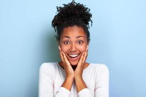 Closeup retrato de una niña bonita sobre fondo azul con asombrada emoción en la cara - imagen foto