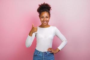 Joven mulata feliz de pie con los pulgares hacia arriba sobre fondo rosa.- Imagen foto