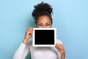 Mockup image of black empty blank screen of tablet in the female hand, peeking from behind tablet over blue background photo