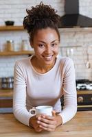 Chica guapa se sienta a la mesa con una taza de té o café por la mañana y sonriendo mirando a la cámara foto