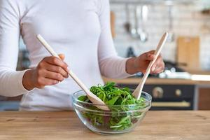 Closeup female hands during cooking a healthy food, stirs with spoons a salad photo