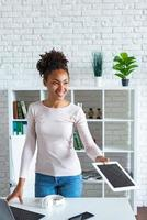 Cheerful woman takes the tablet in office looking straight.- Image photo