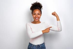 Funny mulatto girl pointing to an herself biceps smiling looking at the camera photo
