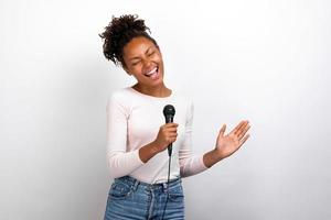 Funny mulatto woman singer holds a microphone in her hands against a ligth studio background photo