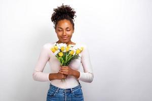 Retrato de estudio de medio cuerpo de una chica maravillosa con ramo de flores, tulipanes y margaritas en sus manos foto