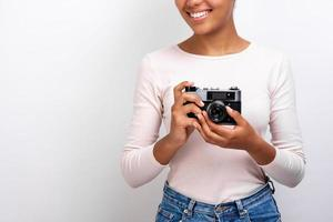Cropping studio image of a mulatto traveller girl holding photo camera in her hands - Image