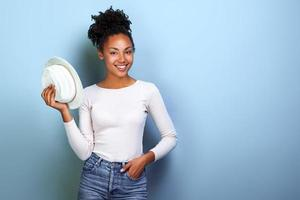 Happy african american traveller woman holds hat and looking at the camera over blue background.- Image photo