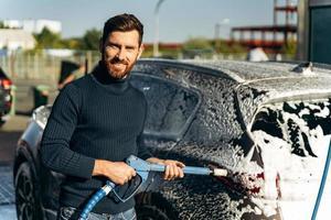 cintura para arriba retrato del hombre que sostiene un rociador de agua a alta presión para el lavado de automóviles. concepto de desinfección y limpieza antiséptica del vehículo foto