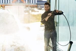 Car wash. Happy caucasian man washing car at the special place. Car wash with high pressure gun concept. Stock photo