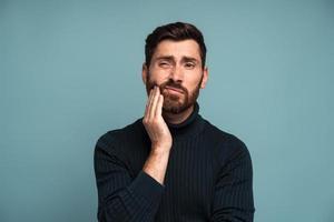 problemas dentales. Retrato de hombre insalubre presionando dolor en la mejilla, que sufre dolor de muelas agudo, enfermedad periodontal, caries o dolor de mandíbula. Foto de estudio de interior aislado sobre fondo azul.