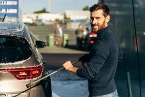Vista vertical de cintura para arriba del hombre lavando su auto en la calle usando una hidrolimpiadora de alta presión con espuma. placer masculino sonriendo a la cámara foto