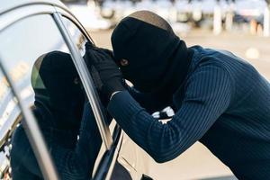 Man dressed in black with a balaclava on his head looking at the glass of car before the stealing. Car thief, car theft concept photo